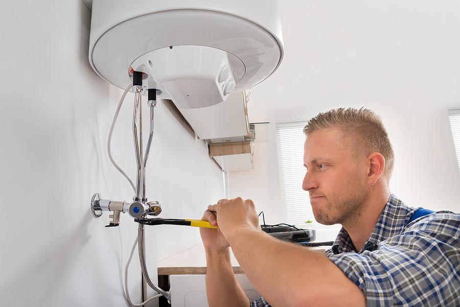 repairman repairing electric boiler with wrench at home