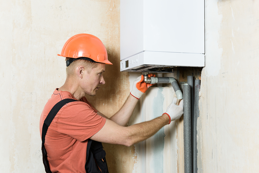 worker is connecting the pipes to a domestic gas boiler.